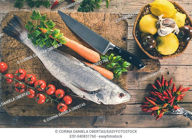 Shi drum fish (Umbrina cirrosa) on old wooden board with carrot, cherry tomatoes, black tomatoes, lemon, garlic, parsley and chili peppers, top view shot