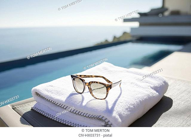 Sunglasses on folded towel at sunny luxury poolside
