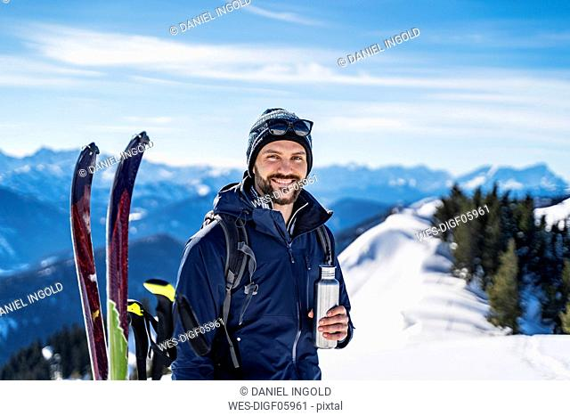 Germany, Bavaria, Brauneck, portrait of smiling man on a ski tour in winter in the mountains having a break