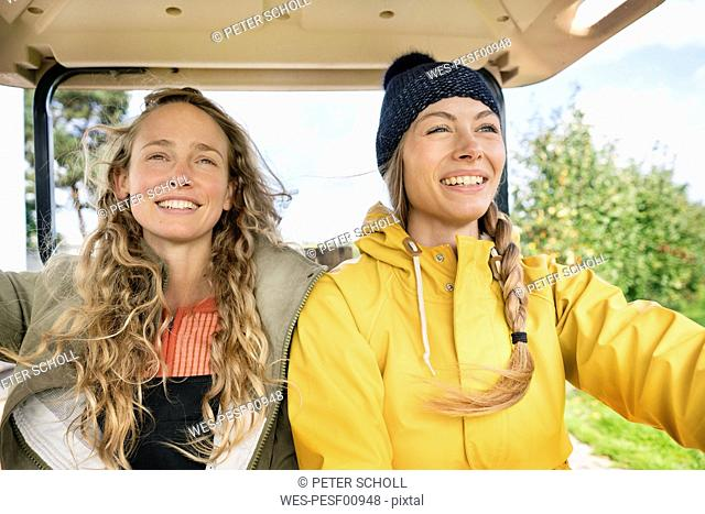 Two smiling women on a tractor