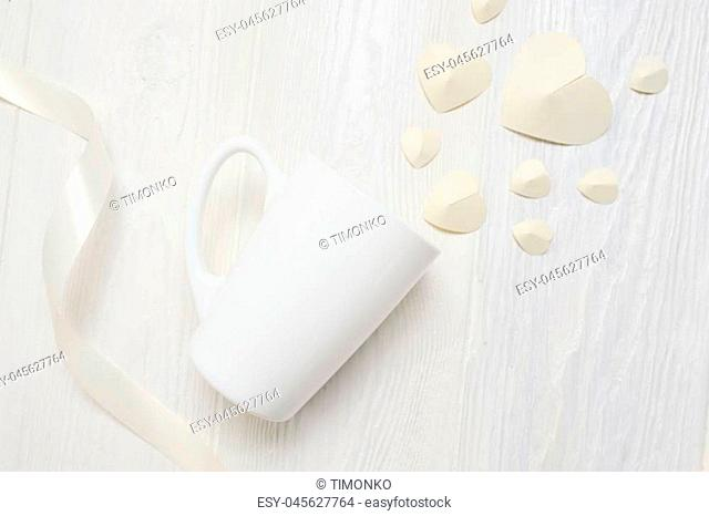 Mockup for St. Valentine's Day greeting card. mug and white paper heart flatlay on a white wooden background, with place for your text