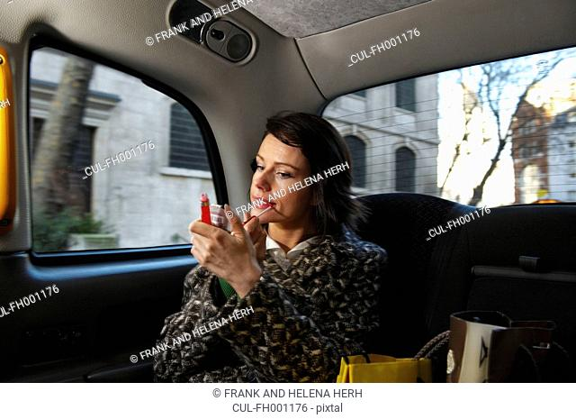 Woman checking make up in taxi