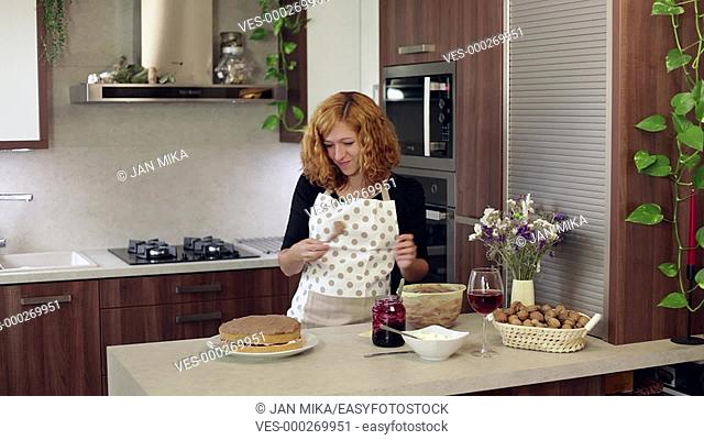 Young happy woman putting cream on homemade cake in the kitchen at home