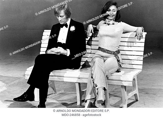 Raffaella Carrà and Nino Ferrer sitting on a bench. Dancer and presenter Raffaella Carrà sitting on a bench with Italo-French Nino Ferrer during the TV...