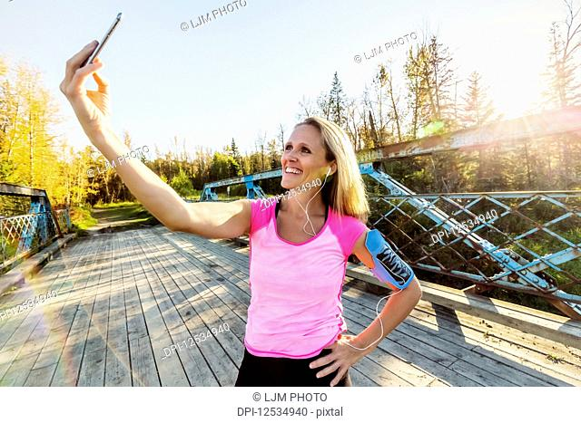 A woman wearing active wear and an arm band for her cell phone stands on a bridge in a park in autumn taking a self-portrait with her cell phone; Edmonton