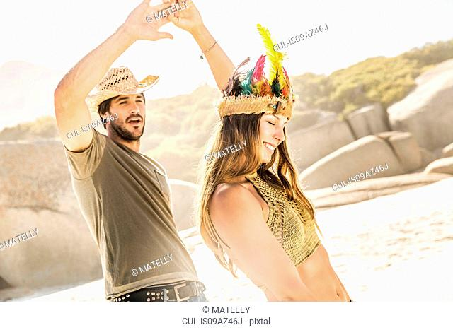 Mid adult couple wearing straw hat and feather headdress dancing on beach, Cape Town, South Africa