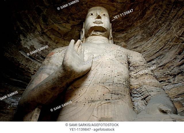 Giant Buddha statue carved inside the ancient Yungang Grottoes, Datong, Shanxi, China