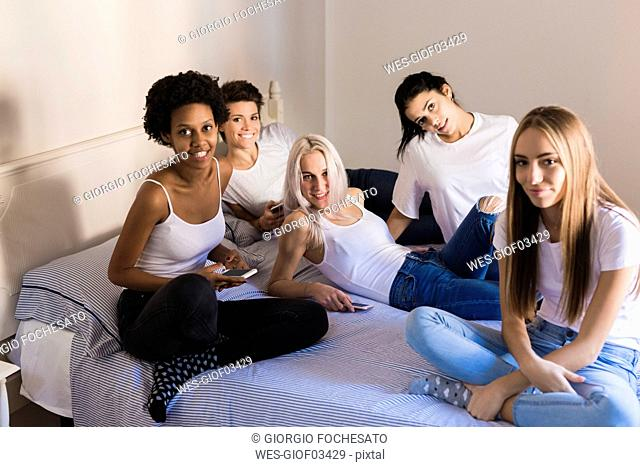 Portrait of female friends with cell phones in bedroom