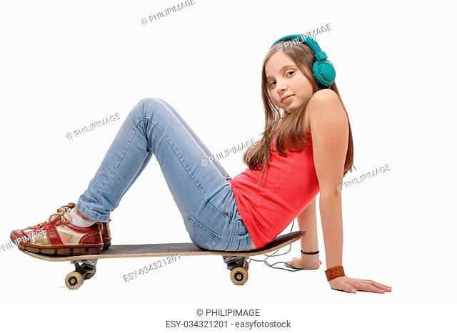 a pretty young girl posing with a skateboard, sitting on skate, on white