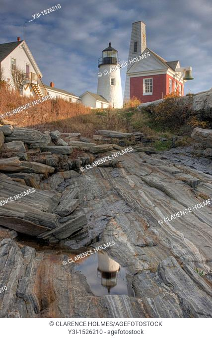 Pemaquid Point Lighthouse and its reflection in a tidal pool, looking up the slope of metamorphic rock formations, Bristol, Maine, USA
