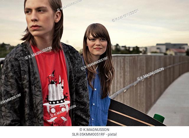 Teenagers with skateboard on walkway