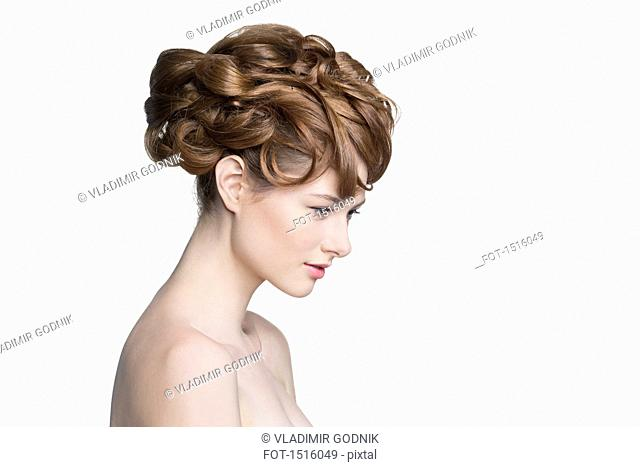 Side view of beautiful woman looking down against white background