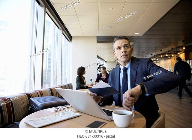 Businessman with airplane ticket checking the time on wristwatch in airport lounge