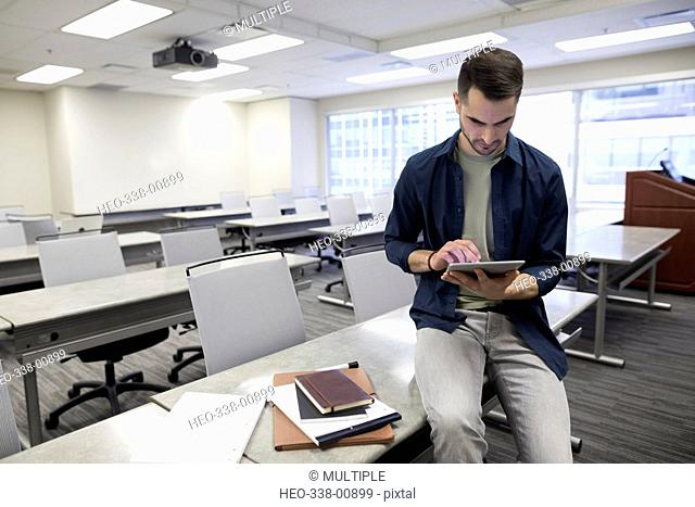 Businessman using digital tablet in empty classroom