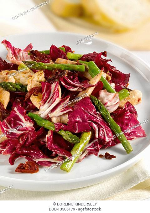 Warm chicken salad with asparagus and red cabbage on plate, close-up