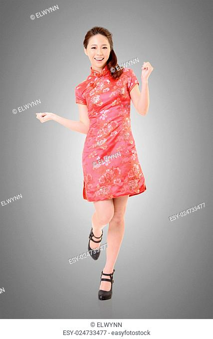 Smiling Chinese woman dress traditional cheongsam at New Year, studio shot isolated
