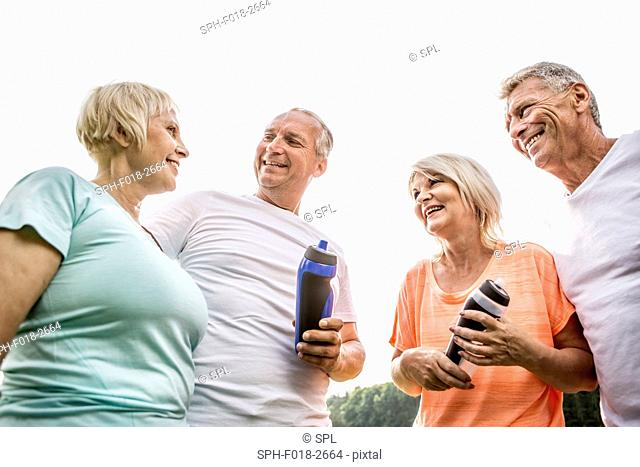 MODEL RELEASED. Four people outdoors with water bottles