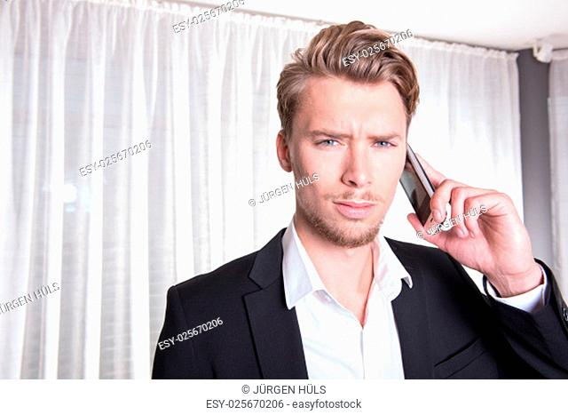 portrait angry young business man in suit on the phone