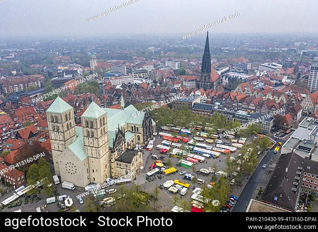 30 April 2021, North Rhine-Westphalia, Münster: In front of the cathedral (l) the weekly market is taking place. In the background you can see the...