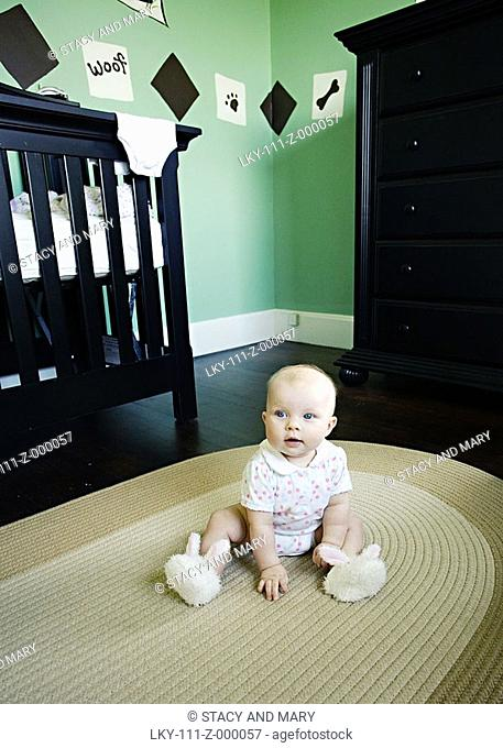 Portrait of baby sitting on bedroom floor