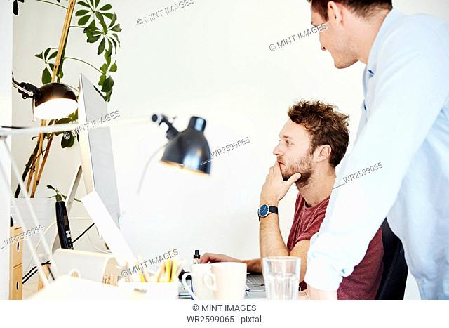 Two men working together, looking at a computer screen