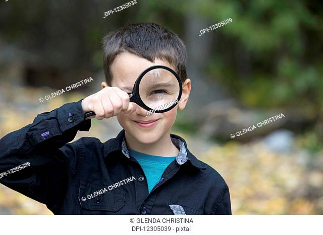 Young boy playing with a large magnifying glass, Palmer, Southcentral Alaska, autumn
