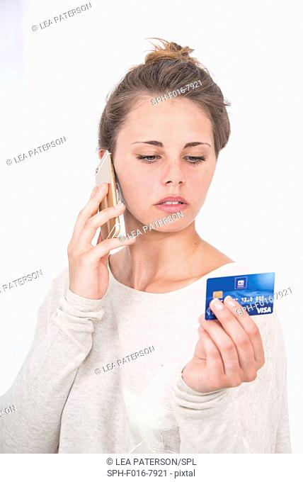 MODEL RELEASED. Woman on mobile phone with credit card, studio shot