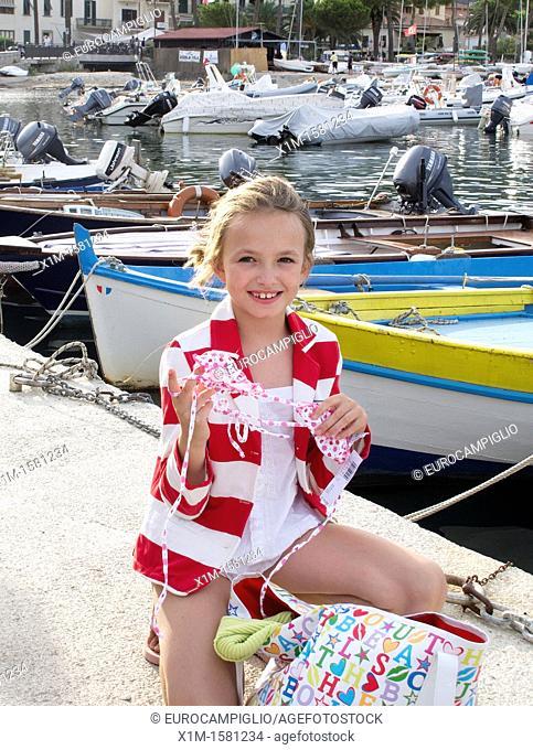 Girl on dock showing her bikini