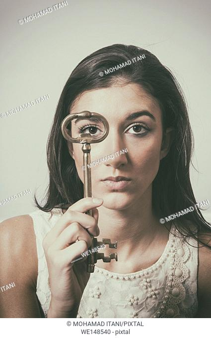 Young woman holding a metal key in front of her face