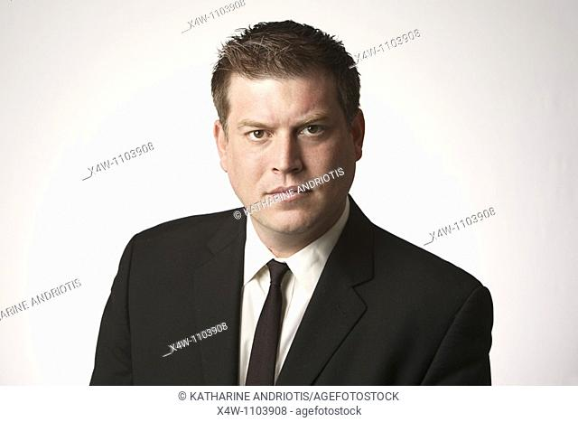 Serious midadult man wearing black suit and tie