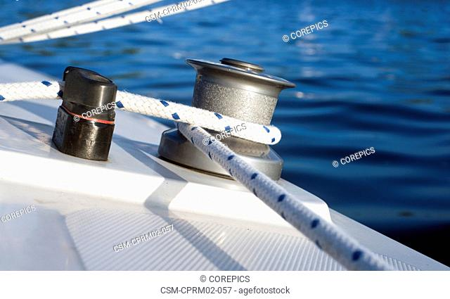 Winch, sheet, and clamp of a small dinghy in the evening light