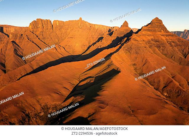 Aerial photo of red sunrise light on the Cathedral Peak region of the Drakensberg. Cathedral Peak Region, Ukhahlamba Drakensberg Park, South Africa