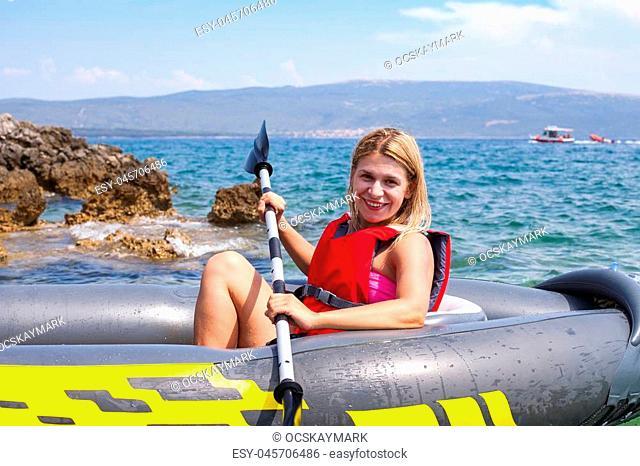 Happy young woman kayaking in the adriatic sea, near by Krk island, Croatia