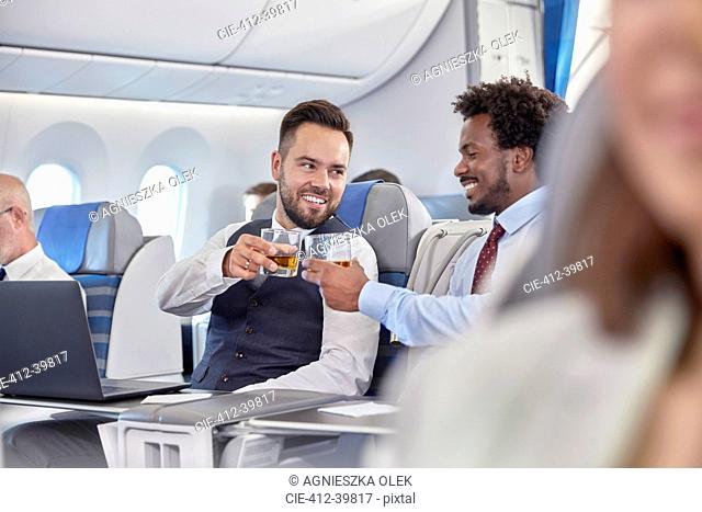 Businessmen toasting whiskey glasses in first class on airplane