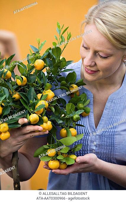 Woman looking at kumquat