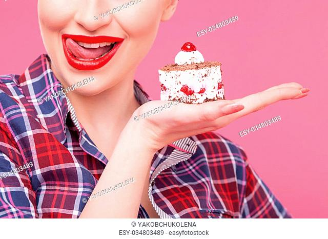 I want to eat this now. Pretty pin-up girl is holding a piece of sweet cake. She is licking her lips with tongue and smiling with desire. Isolated