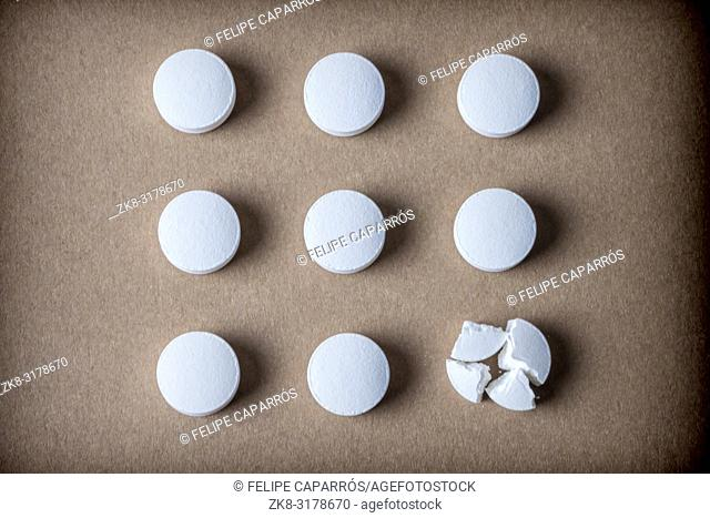 Some isolated white capsules aligned on brown background, conceptual image