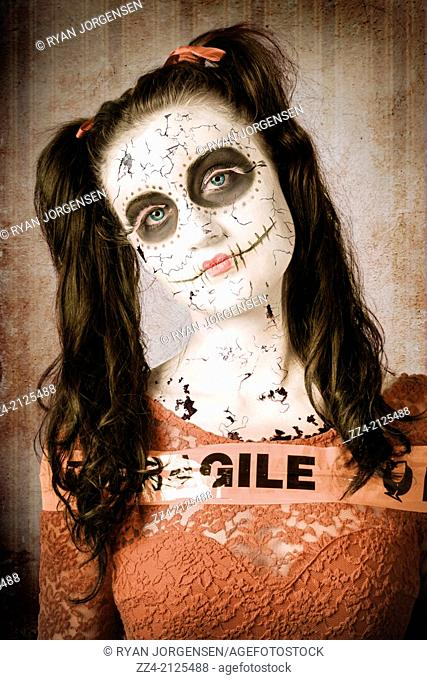 Fine artwork portrait of a human sugar skull doll with cracked porcelain face wrapped in fragile packing tape. Bent and broken