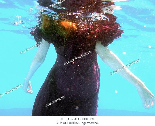 Woman wearing purple dress underwater her arms stretched out to the sides