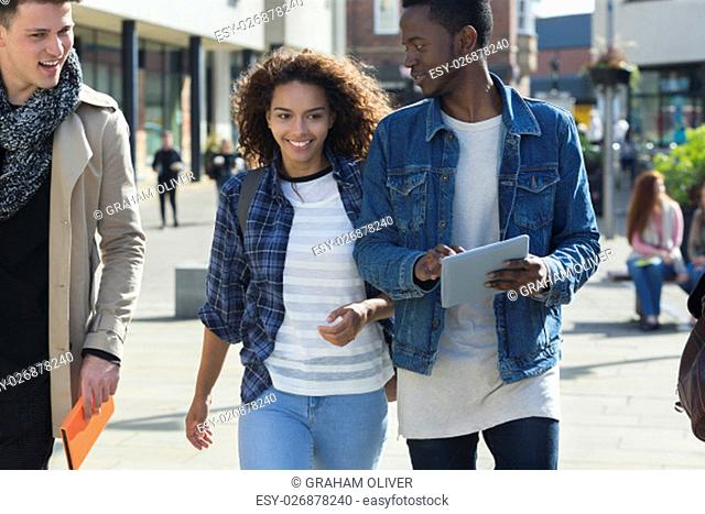 A happy young couple smiles as they take a stroll through the city centre with friends while on a break from university. The male is carrying a digital tablet...