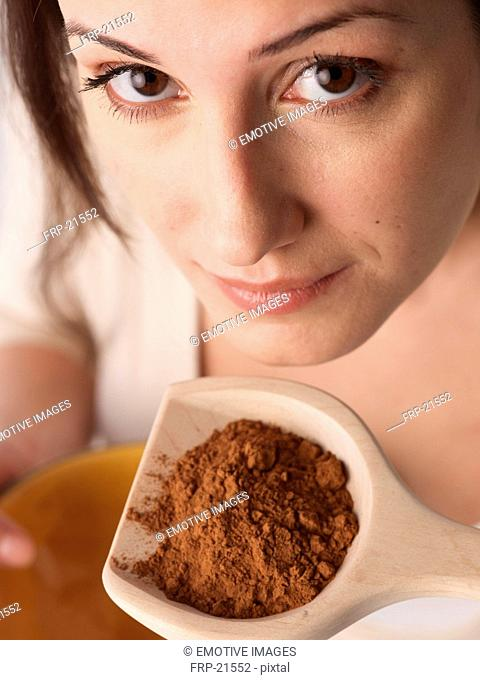 Woman holding wooden spoon with spice