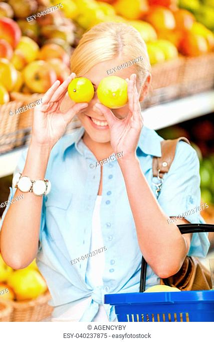 Girl at the shop choosing fruits and vegetables hands lemons and full of purchases hand cart