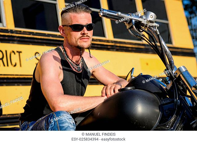 Tough guy with sparrow beard, undercut, black rip shirt and sun glasses lolling on his chopper motorcycle in front of a yellow, American school bus.