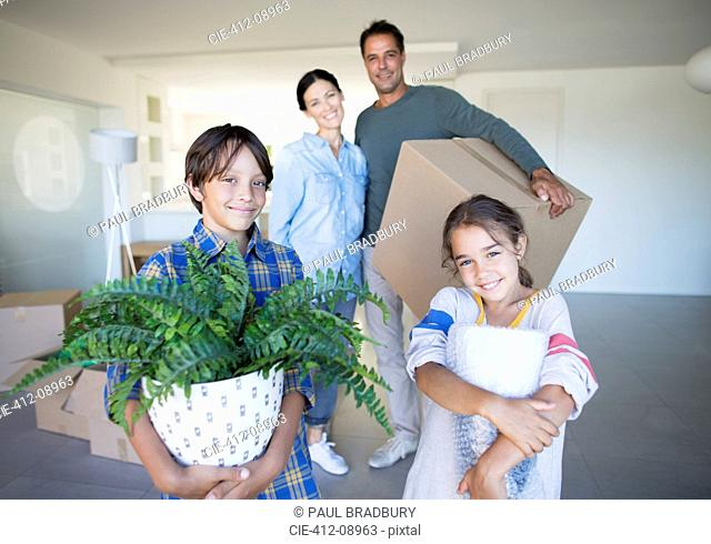 Portrait of smiling family holding belongings in new house