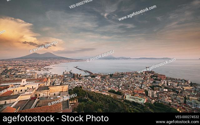 Naples, Italy. Top View Skyline Cityscape In Evening Lighting. Tyrrhenian Sea And Landscape With Volcano Mount Vesuvius. City During Sunset And Night...