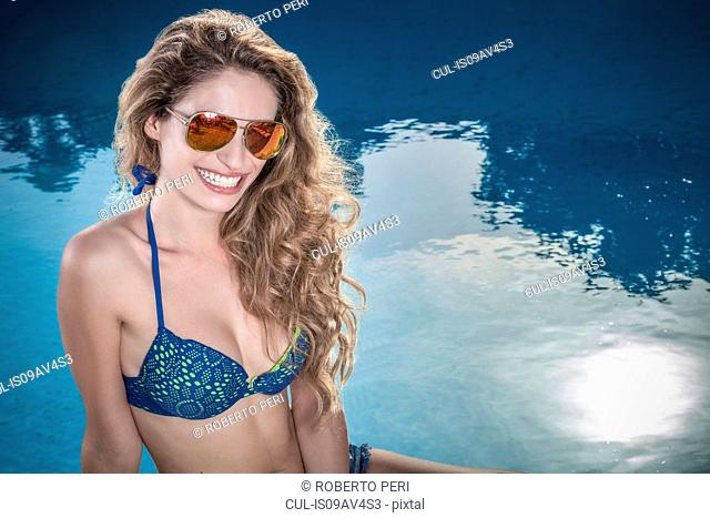 Portrait of teenage girl with long wavy hair sitting at poolside wearing bikini