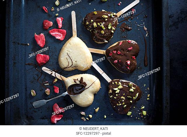 Heart shaped vegan cakes on sticks, decorated with a dark beer glaze, freeze-dried strawberries and pistachios
