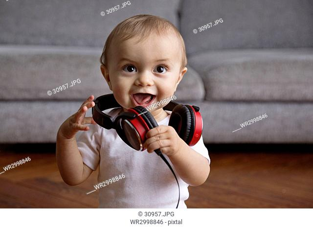 Baby boy with blond hair sitting on hardwood floor, playing with headphones