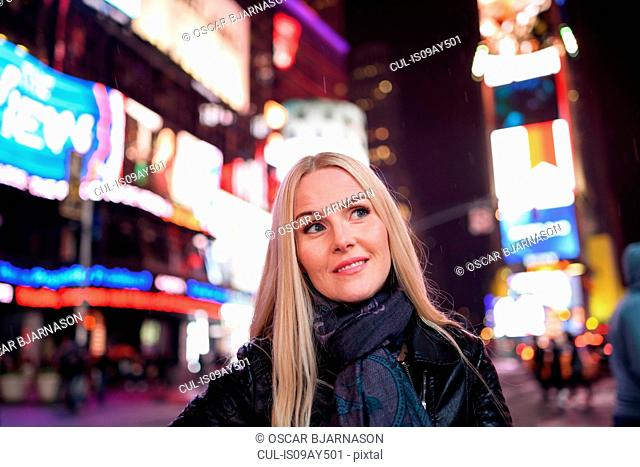 Female tourist in Times Square at night, New York, USA