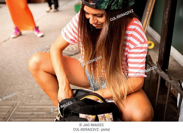 Young woman searching her rucksack on street, Copacabana town, Rio De Janeiro, Brazil